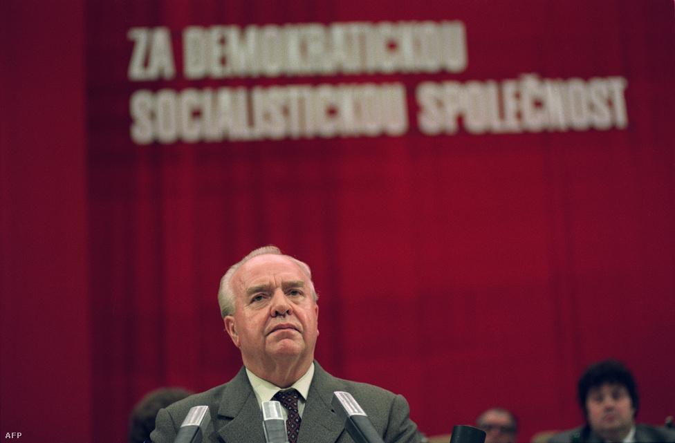 """A kommunista pártkongresszus záró epizódja, háttérben az elhomályosuló """"demokratikus szocialista társadalomért"""" szlogennel, a mikrofonnál Ladislav Adamec, az utolsó kommunista miniszterelnök. Ekkor a keményvonalas főtitkár, Miloš Jakeš már lemondott, és vele együtt az egész Központi Bizottság. Legfeljebb csak utólag lehet ebbe valamiféle történelmi szükségszerűséget képzelni, a valóságban hosszú vita volt, és az is felmerült, hogy bevetik a fegyveres erőket. '89-ből azonban a nemzetközi helyzet miatt sem lehetett újabb '68. Karel Urbáneket választották meg új főtitkárnak, határozatban fejezték ki sajnálatukat a november 17-i események miatt, de párton belüli fejcserékkel már nem lehetett megállítani a """"bársonyos forradalmat""""."""