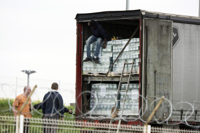 Illegális bevándorlókat szednek le egy kamionról, egy Angliába tartó komp franciaországi kikötőjében.