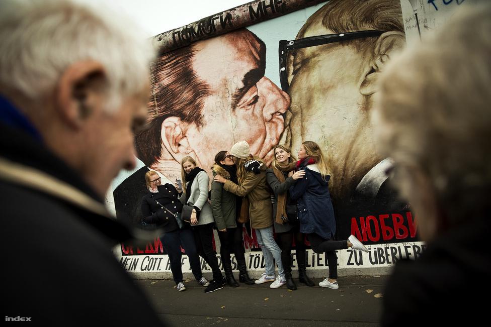 Lányok csókolóznak a csókolózó Brezsnyev és Honecker képe előtt az East Side Gallerynél.