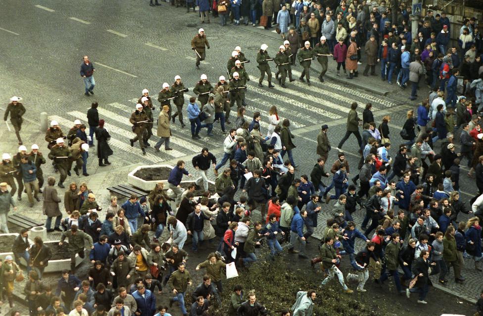 """Húsz évvel később, 1989. január 15-én rohamrendőrök szorítják vissza a Vencel téri tüntetőket. A demonstrálók Jan Palachra, a '68-as bevonulás elleni tiltakozásul önmagát felgyújtó mártírra emlékeztek, a tüntetést a rendőrség vízágyukkal, gumibottal, kutyákkal oszlatta fel. Másokkal együtt Václav Havelt is letartóztatták, a felháborodásból napokig tartó tüntetéssorozat lett. A """"Palach-hét"""" csúcspontja január 19. volt, ezen a napon a korábbiaknál is brutálisabb volt a rendőrség. A Vencel téren néhány ezer ember gyűlt össze, de a karhatalom képviselői még többen voltak, minden tüntetőre több rendőr jutott. A Gorbacsovot éltető, Havelék szabadon bocsátását követelő tömeget körbezárták a fehér sisakos rendvédelmisek, a résztvevőket ütötték-vágták, ezernél is több embert tartóztattak le."""