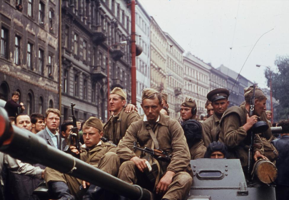 """Orosz katonák a Prágába bevonuló tankokon. Dubčeket orosz fegyveresek a Szovjetunióba hurcolták; néhány nap múlva formálisan visszakapta a pozícióját, hogy nekifogjon saját reformjai lebontásának. A Varsói Szerződés csapatai egy hónap után elhagyták az országot, de az ortodox kommunisták győzelme Gustáv Husák pártfőtitkárrá tételével, a """"normalizáció"""" jegyében kiépített keményvonalas rendszerrel beteljesedett."""