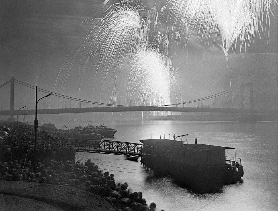 Tüzijáték, háttérben az Erzsébet híd, 1978. Idézet egy korabeli tudósításból: a sötétség beálltával, este 9 órakor röppentek fel a tüzijáték nyitányát jelző világító rakéták, majd megkezdődött a háromnegyedórás műsor. A több tízezres nézőközönség feje felett az esti égbolton egymás után bomlottak ki a színskála különböző árnyalataiban pompázó tűzrózsák. A vizuális élményt a budai oldalt pásztázó nagy teljesítményű fényszórók sugara tette teljessé.