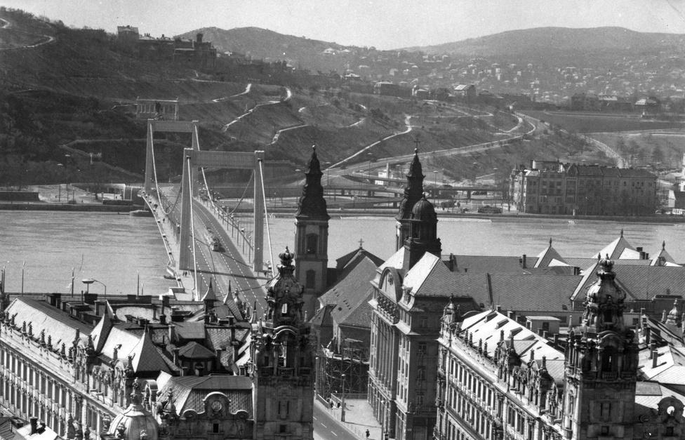 Erzsébet híd, a Belvárosból a Tabán felé nézve, 1966. A vendéglőkkel teli, girbe-gurba utcákból álló Tabánt a harmincas években rombolták le. helyére egy új városrészt képzeltek, de a második világháború keresztülhúzta a számításokat. A városrészt végül a hatvanas években parkosították.