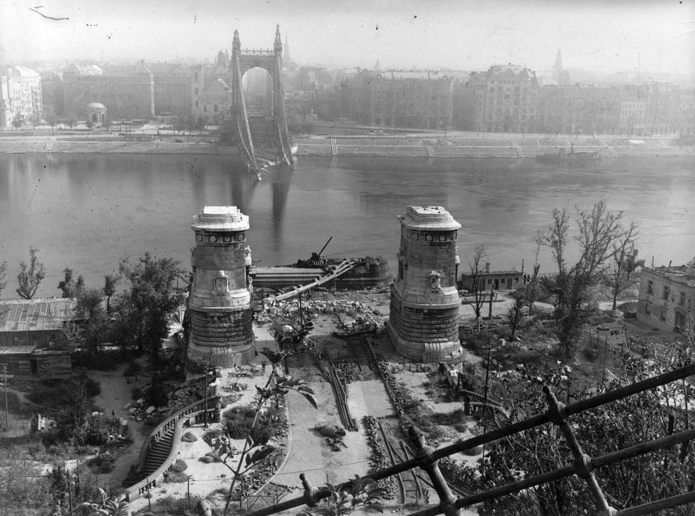 A lerombolt Erzsébet híd a Gellérthegyről nézve, 1945. A hidat január 18-án robbantotta fel a visszavonuló német hadsereg. A töltetek csak a budai hídfő déli lánckamrájában robbantak fel, így a budai oldal pilonja a Dunába zuhant. A pesti hídfő egészen a hatvanas évek elejéig, az új Erzsébet híd építésének megkezdéséig mementóként emlékeztetett a háború pusztítására. 1926-ig ez volt a világ legnagyobb nyílású lánchídja, és nemcsak a legmonumentálisabb, hanem külföldi szakértők szerint a legszebb is. A háború után a korábbi, Erzsébet hídon átmenő villamosvonalak megmaradtak azzal a különbséggel, hogy a pesti, illetve a budai oldalon új végállomást kaptak. A régi Erzsébet hidat újjáépíteni már nem lehetett, kellett egy új híd.