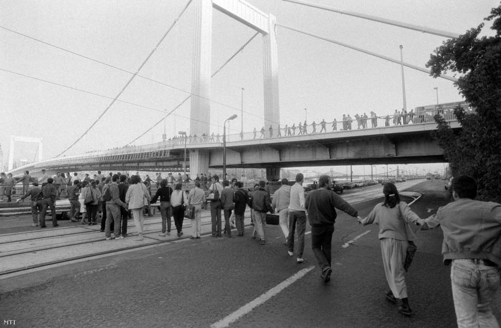 Környezetvédők tiltakoznak az Erzsébet híd lábánál, 1988. október 3. A megmozdulásban résztvevők a Roosevelt tértől a Duna-korzón, az Erzsébet hídon, a Gróza Péter rakparton, valamint az Ybl Miklós téren át a Lánchídig élőláncot alkotva tiltakoztak a bős-nagymarosi vízlépcsőrendszer ellen. A Szabad Európa Rádió szerint a parlament őszi ülésszakának kezdetére időzített akcióban négyezer ember vett részt. A korabeli Országgyűlés a tiltakozást nem vette figyelembe, és megszavazta a vízlépcső megépítését. A magyar oldalon ennek ellenére 1989-ben leállt az építkezés, 1992-ben pedig felbontottuk a szerződést a csehszlovák féllel.