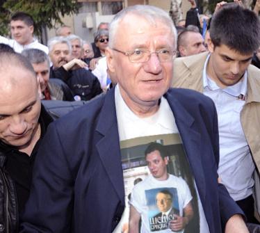 """Šešelj Šešelj-pólót hordó Vučić-pólóban. A """"szerb Hírcsárda"""" Njuz.net mémje paródiája arról, hogy a mentorát megtagadó, jelenlegi miniszterelnök Vučić pár éve még korábbi radikális párttársaival együtt, a parlamentben is Šešelj-pólót viselt."""