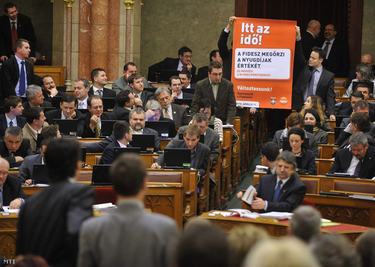 Scheiring Gábor, a Lehet Más a Politika képviselőjének felszólalása alatt frakciótársai egy fideszes választási plakátot tartanak a magasba a nyugdíjreform és adósságcsökkentő alapról és a szabad nyugdíjpénztár-választás lebonyolításával összefüggő törvény végszavazása előtt az Országgyűlés plenáris ülésén.