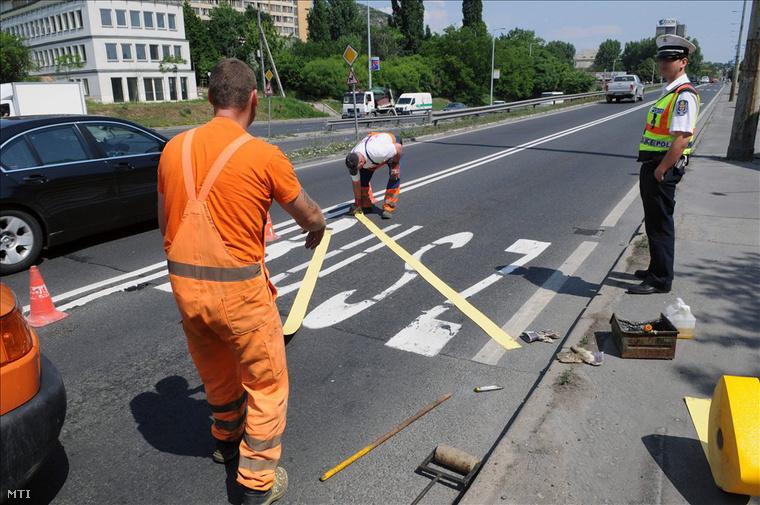 Útkarbantartók leragasztják a buszsávot a Budaörsi úton