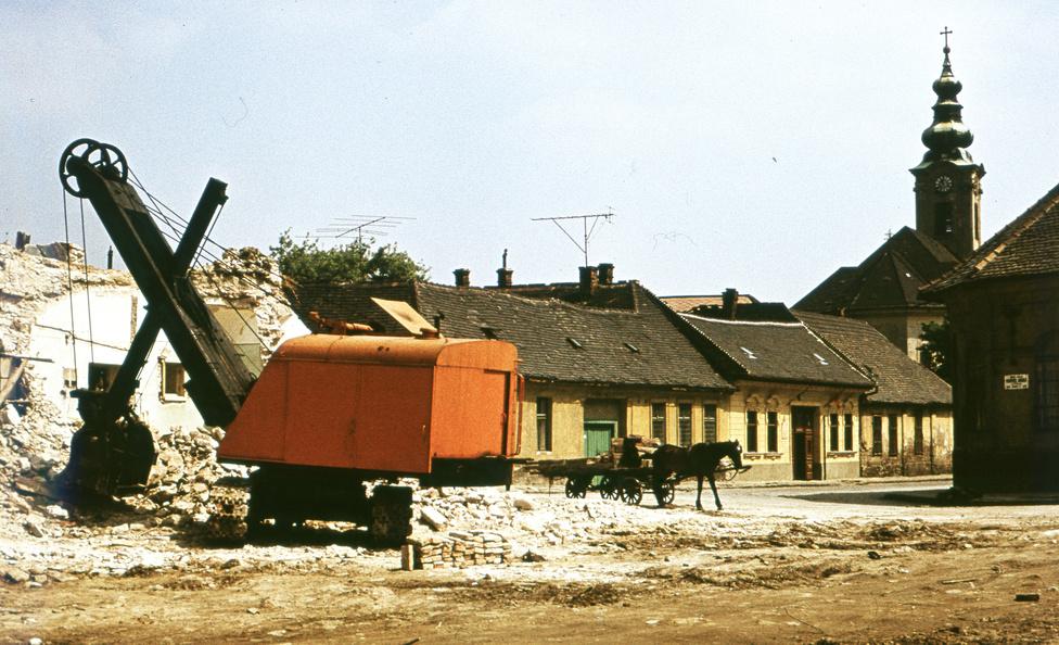 A régi Óbuda megsemmisítése a Kiskorona utcánál. A rossz vályogházakon kívül értékes épületek is a bontás áldozatául estek, olyanok is, amelyeket nem sokkal korábban renováltak. A sváb fuvarosok, borkereskedők lovait, kocsijait még a régi városrész bontásánál használták, utána az állatok mehettek a vágóhídra.