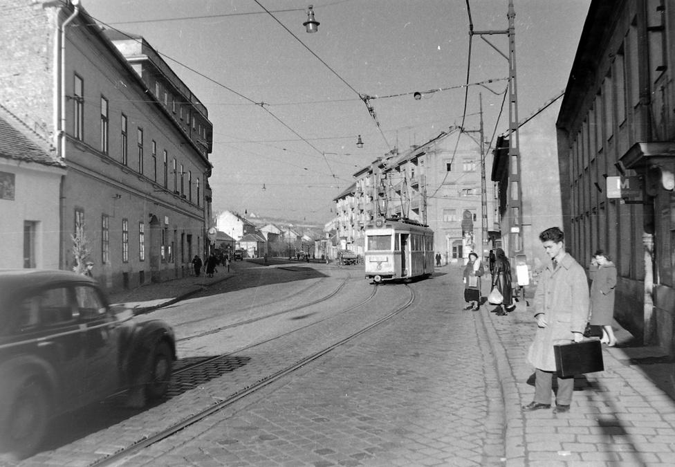 """A Bécsi út a Nagyszombat utcánál, az Amfiteátrum közelében - itt volt régen Óbuda határa. A gyógyszertár előtti óra és hirdetőoszlop afféle lokális randihelyként is funkcionált, az út túloldalán állnak a """"városi házak"""". Ez a rész, ha nem is teljesen érintetlenül, de megmaradt."""