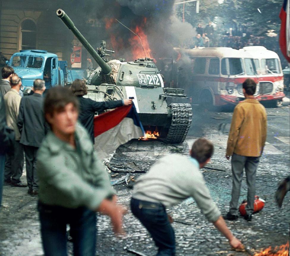 """Égő fáklyák repülnek a prágai tavaszt eltipró szovjet tankokra 1968. augusztus 21-én. Ez a nap nem csak a reformokban messzire menő Csehszlovákia sorsát döntötte el a következő két évtizedre, egész Kelet-Európában is eloszlatta az """"emberarcú szocializmussal"""" kapcsolatos reményeket. A '68 elején hatalomra jutó Dubček alatt nagyjából megszűnt a cenzúra, felerősödtek a szovjetellenes hangok, és gazdasági reformokkal, óvatos piacosítással próbálkoztak. Brezsnyev és keményvonalas szövetségesei – ok nélkül – attól is tartottak, hogy Csehszlovákia a katonai blokkból is fontolgatja a kilépést. A Varsói Szerződés csapatai, köztük a kádári jóváhagyással részt vevő magyar egységek éjfélkor kezdtek átgördülni a határon, '56 után újra világossá téve, hogy Moszkva nem engedi a komolyabb reformokat."""