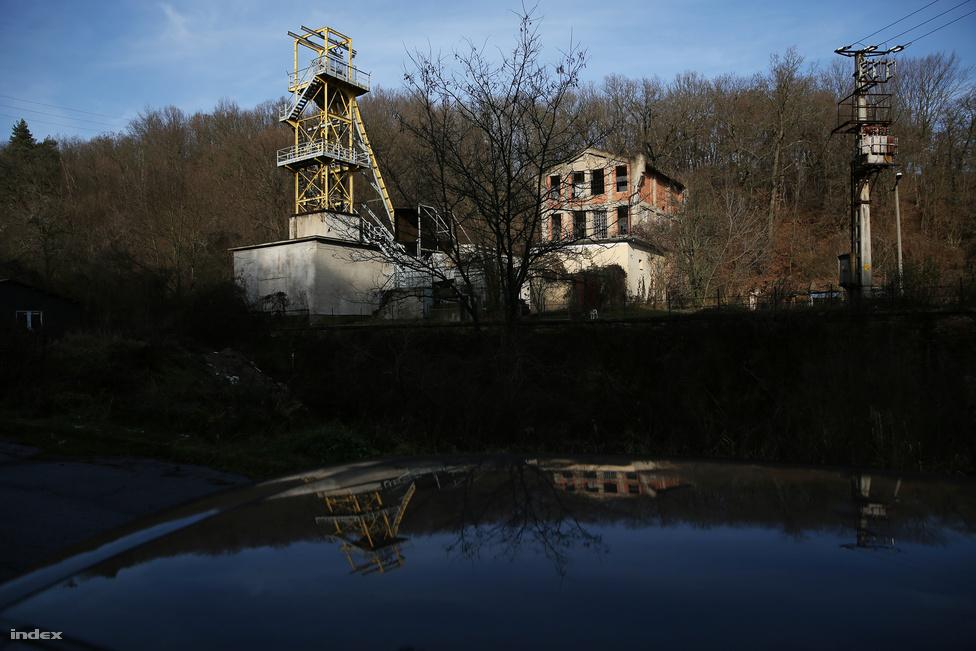 A perecesi bányaüzem üresen álló építményei. A bányaüzembe vezető vaskapu tárva-nyitva áll, beljebb egy-két kisebb vállalkozás működik. A területen csaholó kutyák kószálnak mindenfelé. A bányásztelepülés hanyatlása a hatvanas-hetvenes években, a közeli bányák és aknák bezárásával kezdődött. Bezárt a mozi, a helyi színjátszók nem léptek fel többé a szabadtéri színpadon, megszűnt a kisvasút, boltok húzták le a rolót, és a település egykori legendás, a nagy miskolci klubokkal vetélkedő focicsapata is szépen lassan elindult a megszűnés felé. A környékbeli legenda szerint a föld gyomra még rengeteg szenet rejt, ennek kiaknázásáról választások előtt előszeretettel beszélnek helybeli politikusok.