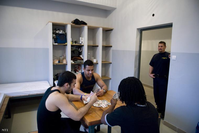 Nabay Seku (háttal) francia guyanai Ferreira Lourence Ezequiel Amarre (b) és Leandro Jose De Souza brazil fogvatartottak kártyáznak a Repülőtéri Rendőr Igazgatóság Őrzött Szállásán 2013. március 14-én.