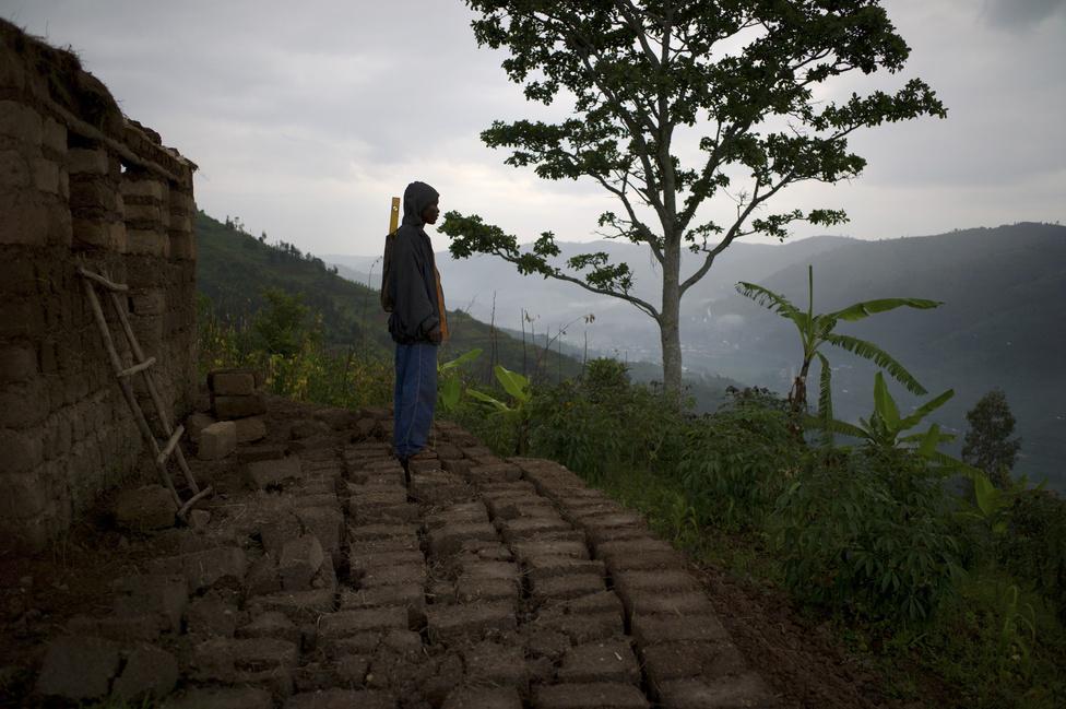 2014. Hat év vándorlás után Angelo hazatér a szülőföldjére, a Mbogo dombhoz, hogy megépítse saját házát. A munkában nagyapja, Wenceslas és testvére, Jean-Paul segítik. A ház keretét fatörzsekből építik meg, az agyagtéglákat Angelo maga készíti. A tető hullámpala.