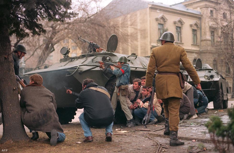 Felfegyverzett civilek és katonák egy páncélozott csapatszállító mögött. Ceaușescu és felesége először csak az egyik vidéki elnöki rezidenciára ment, de onnan tovább kellett menekülniük, és az időközben bevezetett légtérzár miatt autóval próbált eljutni egy reptérhez. A forradalmárok és az átállt rendőrök azonban elfogták őket, és végül  a Târgoviște-nél lévő katonai bázisra kerültek.