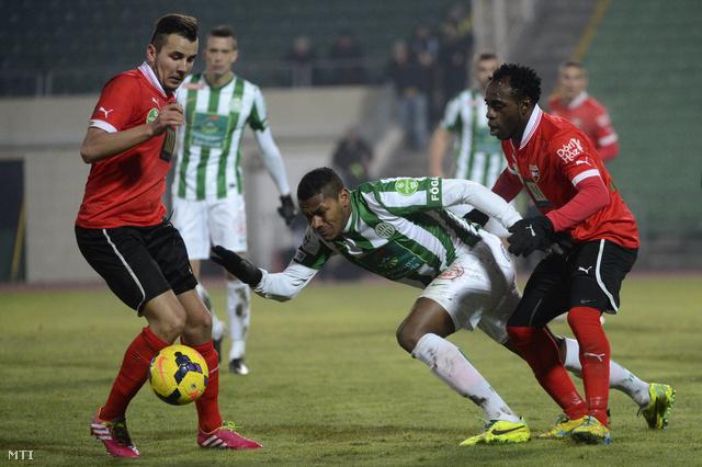 A ferencvárosi Gerson (k) a pécsi Nagy József (b) és Eke Uzoma (j) között a labdarúgó OTP Bank Liga 16. fordulójában játszott Ferencváros - PMFC-Matias találkozón a Puskás Ferenc Stadionban.