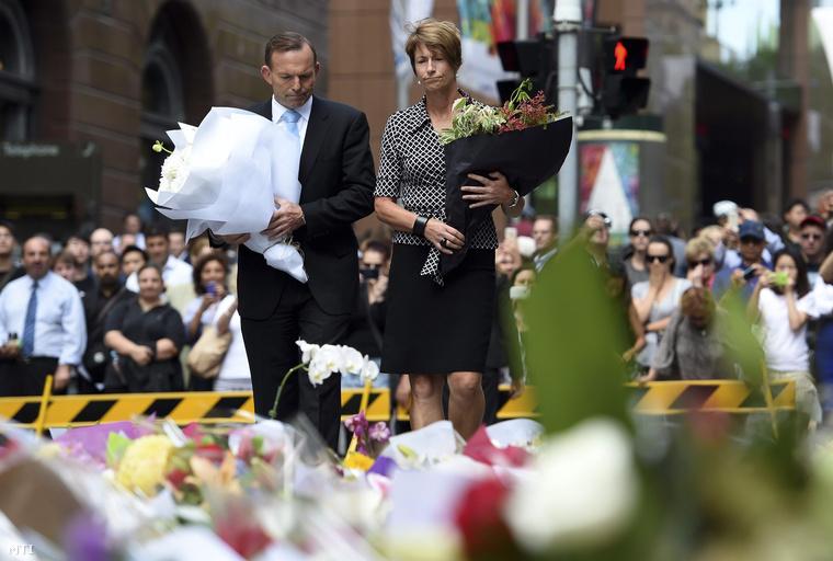 Tony Abbott ausztrál miniszterelnök és felesége Margie virágot helyez el annak a sydney-i kávézónak a közelében 2014. december 16-án ahol az előző napon tűzpárbaj alakult ki egy túszokat ejtő fegyveres férfi és rendőrök között.