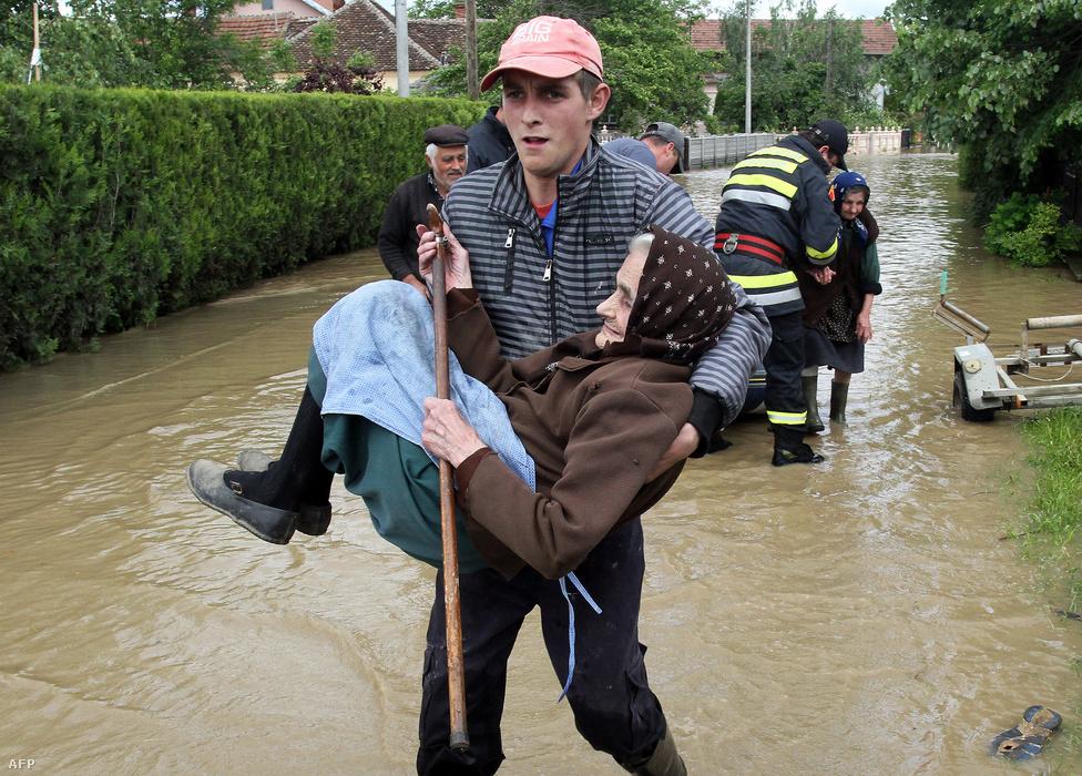 Egy idős asszonyt mentenek május 17-én a                          szerbiai áradások elől. Harminchárman                          meghaltak, több mint 1700 épület összeomlott,                          majdnem 32 ezer embert ki kellett telepíteni.                          Alekszandar Vucsics miniszterelnök szerint az                          árvíz egymilliárd eurós (kb. 314 milliárd                          forintos) kárt okozott.