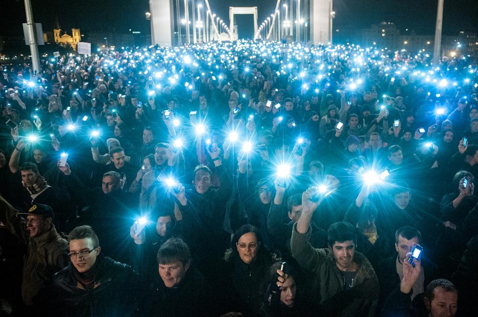 A képet október 28-án készítettem az Erzsébet hídon vonuló több tízezres tömegről, akik az internetadó elleni tiltakozásként egyszerre tartották a magasba mobiltelefonjaikat. A hírkép készítésénél dilemmában voltam, hogy a legtöbb kollégához hasonlóan a Gellért-hegyről fényképezzek-e, vagy maradjak a hídon és egy magasba tartott egylábú állvánnyal dolgozzak. Végül utóbbit választottam, mert így nemcsak a tömeg, de a vonulók arcai is látszódnak, ezáltal pedig sokkal személyesebbnek érzem a fényképet.