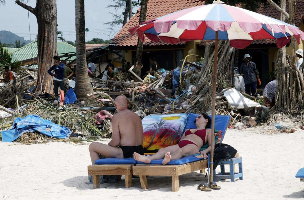 Turisták napoznak hat nappal a katasztrófa után Phuket szigetén, miközben a háttérben még takarítják el a törmeléket a parton. Tíz évvel a pusztító cunami után már sok partmenti város és halászfalu újjáépült, a túlélők pedig új életet kezdtek.