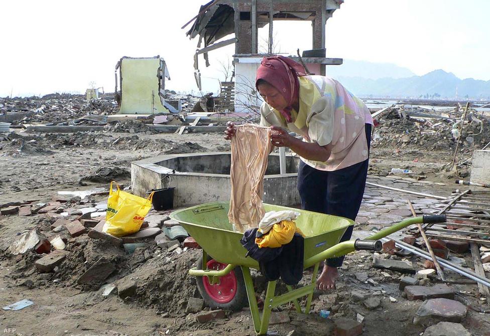 Egy indonéz asszony egykori háza romjainál mossa a ruháit két és fél hónappal a cunami után. Indonézia kormánya azt ígérte, hogy 2005 márciusában nekikezdenek az újjáépítéseknek.