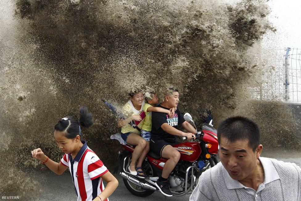A Csien-tang folyó vize kilépett medréből augusztus 13-án a heves zivatarok és a torkolatánál fellépő dagály miatt. A képen éppen a felcsapó hullámok elől menekülnek a bámészkodók.