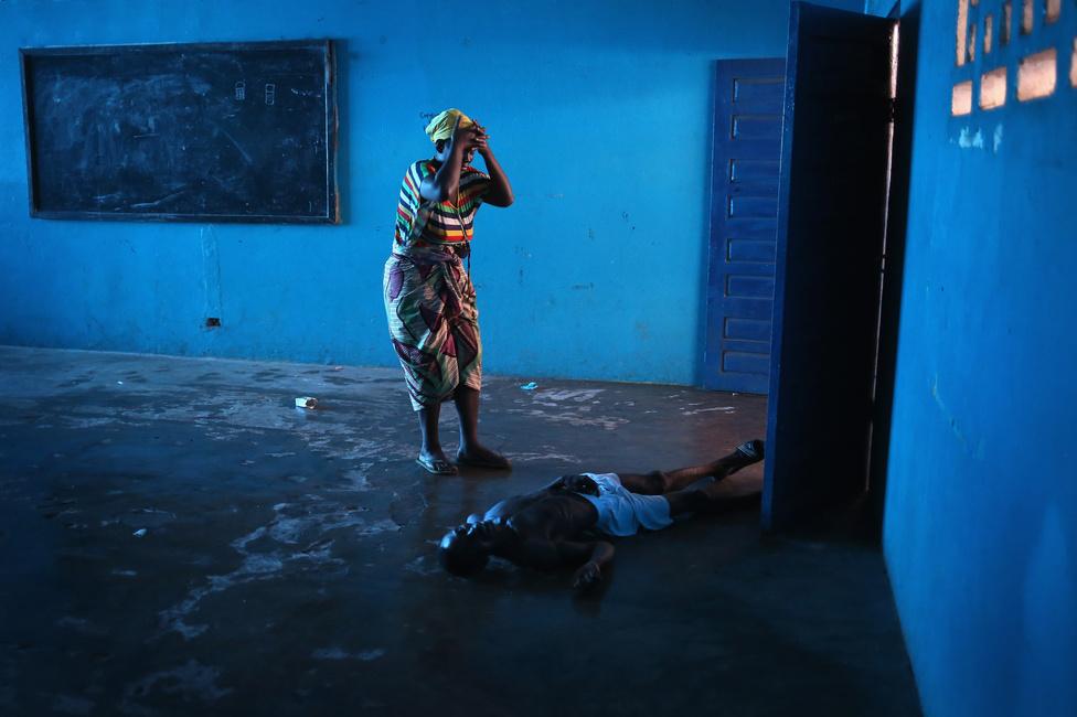 Egy asszony az elájult férje felett egy elkülönítőben Libéria fővárosában, Monroviában augusztus 15-én. A még feltehetően 2013 decemberében Sierra Leonéban kezdődött ebolajárvány két másik afrikai országban, Libériában és Guineában is sok áldozatot követelt. Az Egészségügyi Világszervezet (WHO) december 30-i jelentése szerint a fertőzöttek száma az ebola által leginkább sújtott három afrikai országban együtt már meghaladta a 20 ezret, és eddig 7842 ember halt meg a járványban. Nigériában és Maliban is voltak megbetegedések, az Egyesült Államokban pedig egy Libériából érkezett férfi halt meg a betegsében. Két amerikai és egy spanyol nővér is elkapta a betegséget, de ők azóta már meggyógyultak.