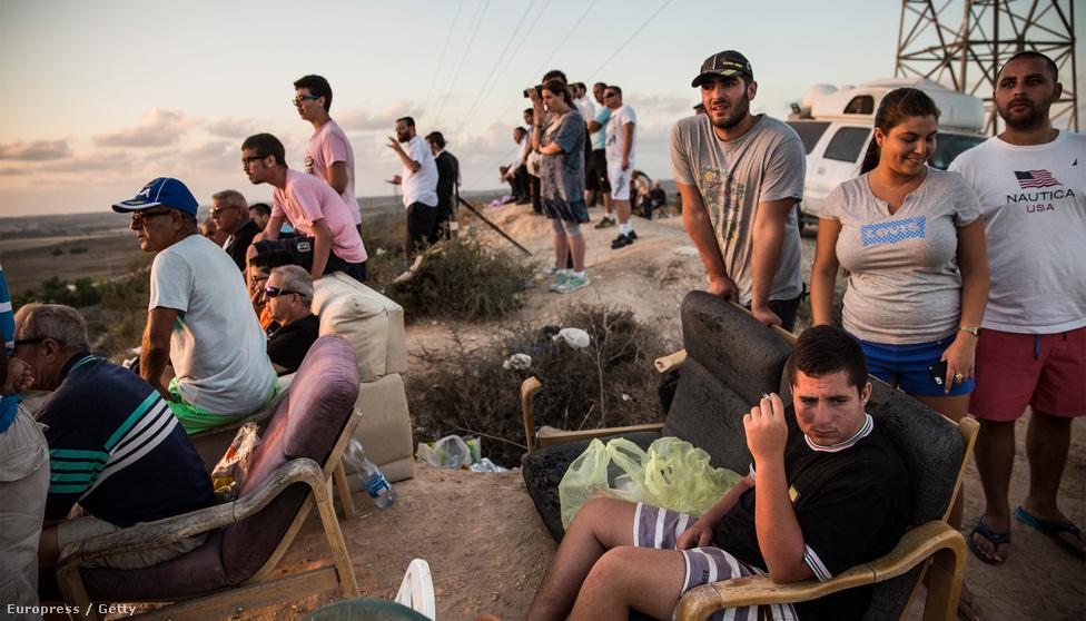 Izraeliek nézik a közeli hegyről a Gázai övezet elleni légi csapásokat július 14-én. A Hamász újabb rakétatámadásokat indított a Gázai övezetből, Izrael pedig először intenzív légi csapásokba kezdett, majd július 17-én szárazföldi offenzívát indított. Ennek célja az izraeli vezetés szerint a Hamász sokezres rakétaarzenáljának megsemmisítése mellett a területről Izraelbe vezető alagútrendszer felszámolása. A július 8-án kirobbant konfliktusban a gázai hatóságok állítása szerint több mint 2100 palesztin vesztette életét, az áldozatok többsége civil volt. Izraeli részről 64 katona és öt civil halt meg. Az 1,8 milliós Gázai övezetben a helyi hatóságok szerint több mint félmillió embernek kellett elmenekülnie otthonából. Az izraeli–palesztin konfliktust körbelengő legfontosabb kérdésekről, a háború utáni dilemmákról itt olvashatja bővebb elemzésünket>>>