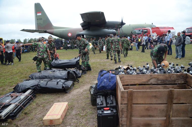 Az AirAsia lezuhant repülőgépének roncsai közelében talált holttesteket az indonéz légierő tagjai a Borneó szigetén fekvő Penkalan Bun támasztpontra szállítják, 2014. december 30-án.