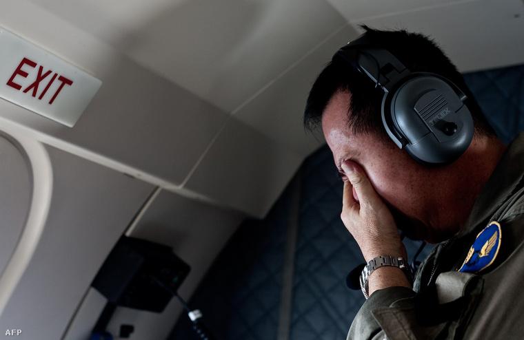 Egy hozzátartozó a kutatás végző repülőgép fedélzetén, 2014. december 30-án. Három napig kutattak az Indonézia légterében vasárnap eltűnt utasszállító gép után, a keresést még a szárazföldi területekre is kiterjesztették, ám a repülőgép roncsaira végül a tengeren találtak rá.