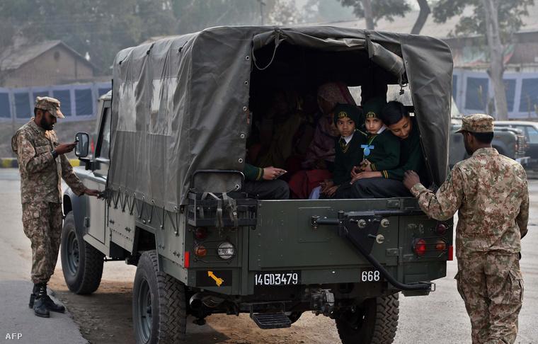 Katonai teherszállítóval viszik iskolába a gyerekeket Peshavarban.