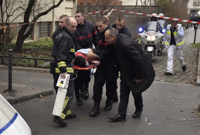 A Charlie Hebdo szerkesztőségét ért támadás egyik sérültjét szállítják el az épületből, 2015. január 7-én.