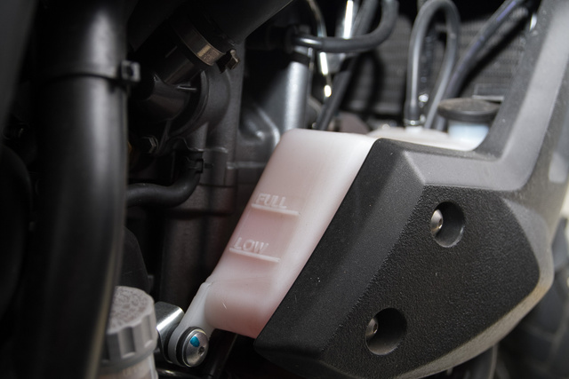 A kiegyenlítőtartály szintje legyen minimum és maximum között, ha a motor egyenesen áll. A kiegyenlítőtartályt bátran kinyithatjuk, nincs nyomás alatt