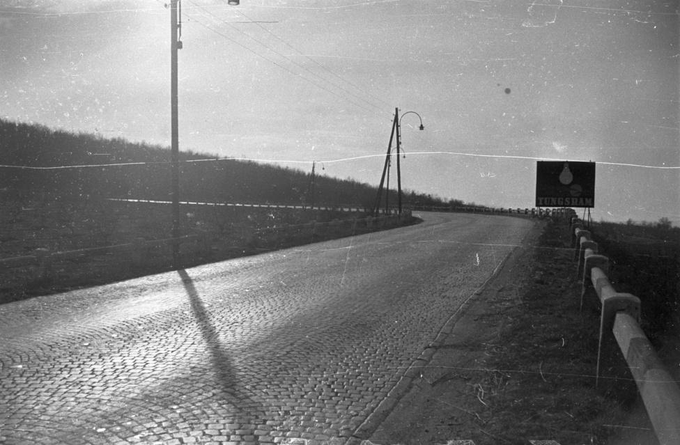 Ez a Lepsénynél még megvolt korszaka. A régi 7-es út hajtűkanyarja a városkapu után. Ennél a  furmányos emelkedőn forrt fel a hűtővíz a régi Skodákban, Volgákban, Warszavákban, ott szentségeltek az út szélén a kor apukáig a nyitott motorháztetők mellett. A képen a korabeli óriásplakát érdemel még figyelmet: a Tungsramot reklámozza, nem mintha 1960-ban olyan nagy lehetőségünk lett volna bármilyen más égőt vásárolni.
