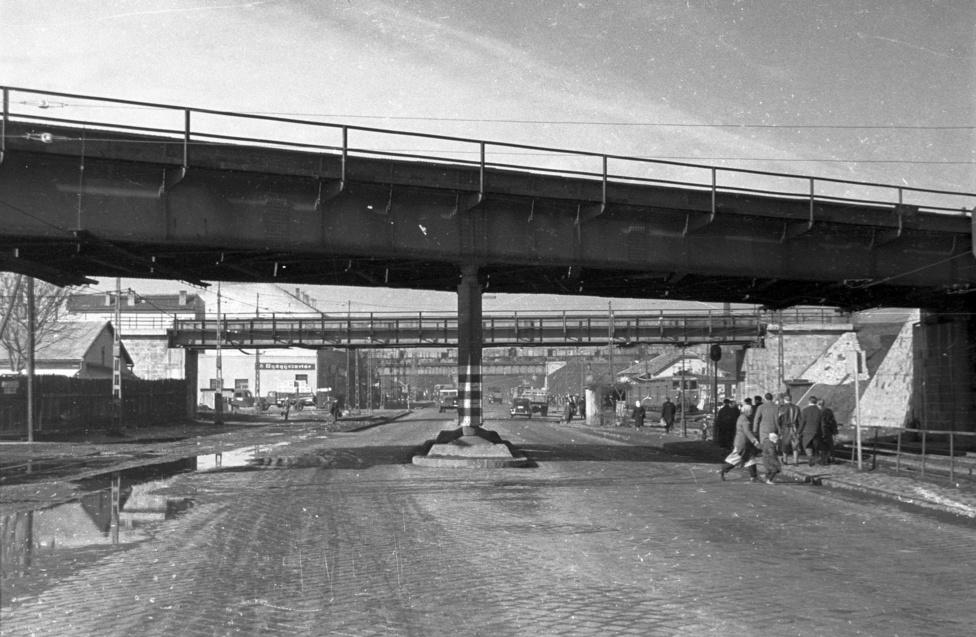 A macskakő, az útszéli pocsolya, az ipari táj azt sejteti, hogy valamelyik szocialista iparvárosban járunk, de nem. Innen autóval 1960-ban is csak alig negyed óra volt a Parlament épülete. Akik az autópálya előtti világban Szegedről jöttek föl Pestre, azoknak a retinájukba égett a látvány: Soroksári út, a csepeli leágazás után a város és a Déli összekötő vasúti híd felé nézve. Az ember a végtelennek tetsző Soroksári út végigautózásával jutott el idáig, ahonnan már tényleg csak egy ugrás a város.