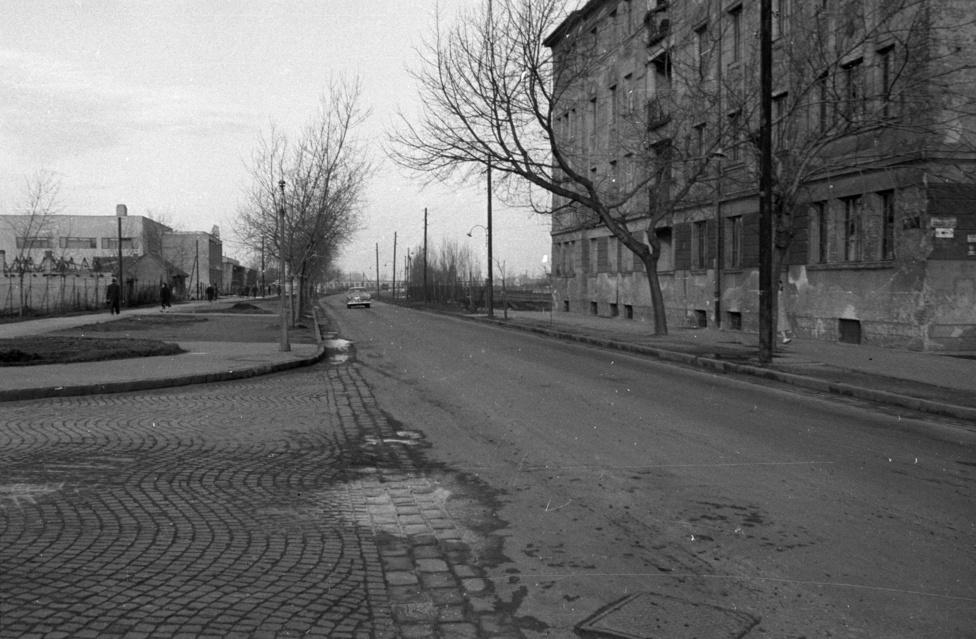 Helló, 1960! Ez itt már a szép, új világ, csak azt az ócska bérházat kéne eltüntetni a kép jobb oldaláról. Balra, távolabb a még mindig egészen újnak számító Dagály fürdő fejépülete, a balra vezető macskaköves út pedig az 1939-ben elkezdett, de a háború miatt csak 1950-ben befejezett Árpád hídra vezet. (Legalább nem volt ok lebombázni a félkész hidat.)