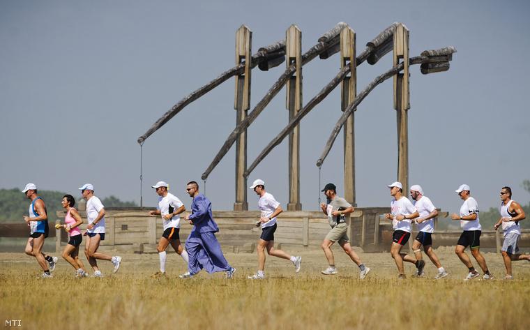 Résztvevők futnak el egy négyállásos gémeskút előtt a Hortobágyon megrendezett Délibáb félmaratonon.