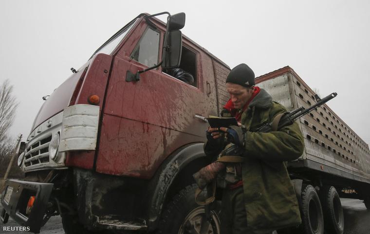 Oroszpárti szeparatista ellenőrzi egy sofőr papírjait a donyecki úton