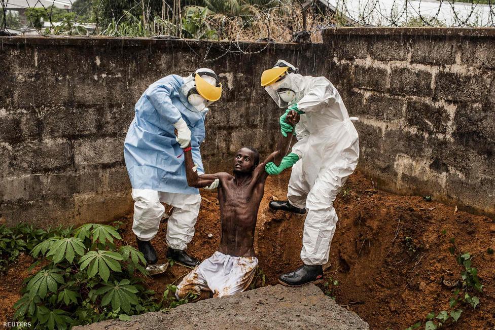 Hír kategória, első hely: egy végső stádiumos ebolás beteget emelnek ki az őrök a gödörből, aki hallucinálni kezdett és szökni próbált a karanténból. A férfi nem sokkal a kép készítése után belehalt betegségébe.
