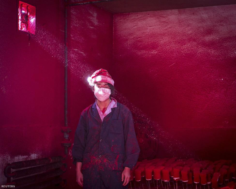 Korunk problémái, első hely: egy kínai munkás portréja, aki egy karácsonyi tárgyakat gyártó üzem szalagja mellett dolgozik.