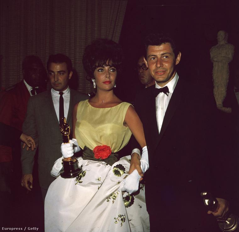 1961, Elizabeth Taylor akkori férje,  Eddie Fisher énekes-színész karján suhan, kezében a Modern kaméliás hölgyért kapott díjával.