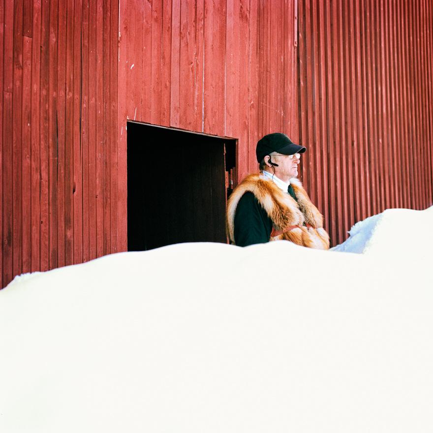 """Erki Orre rénszarvasverseny-edző nézi az edzést a finnországi Rovaniemiben. A rénzzarvasversenyzés egy rendkívül népszerű sport a számi kultúrában. A versenyzők több számban is indulhatnak: az elterjedtebb és az ember számára bonyolultabb válfajbcsak rénszarvasok sítalpakon csúszó """"zsokákat"""" húznak, míg a másik, inkább a rénszarvasnak megerőltető műfajban szánkót kötnek a szarvas után. Rovaniemiben minden évben március első heteiben, a közelgő tavasz üdvözlésére rendezik meg a nagy rénszarvasversenyt. A versenyt a drámai hatás kedvéért naplemente előtt kezdik, a versenyzők körönként esnek ki, míg végül csak ketten maradnak a döntő összecsapásra. A 12 méteres rénszarvassprint világrekordja 2013-ban egyébként 14,92 másodperc volt."""