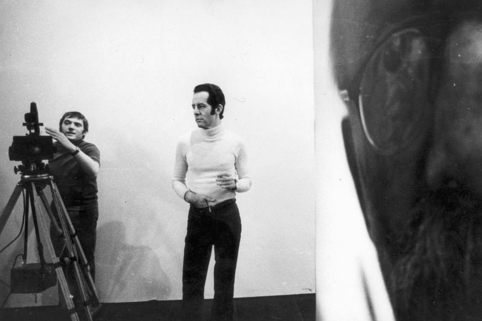 Noha Schiffer Pált főleg a szociológiai filmjeiről ismerik, azért csinált mást is: itt éppen Féner Tamás fotóművész 1972-es Műcsarnok-beli kiállításán forgat.