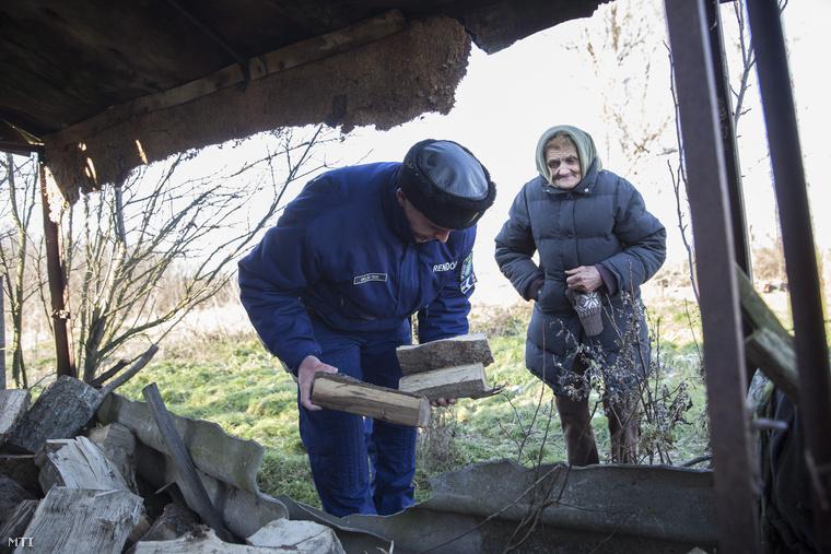 Rendőr segít egy idős nőnek tűzifát pakolni egy Szarvas környéki tanyán, 2014. december 30-án.A Békés Megyei Rendőr-főkapitányság bűnmegelőzési osztálya és a helyi tanyaprogramban részt vevő rendőrök kiemelt figyelmet fordítanak a tanyákon élő idős emberekre a hideg idő beálltával.