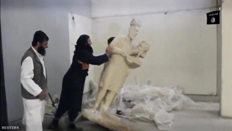Jelenet egy videóból, amin az Iszlám Állam tagjai szobrokat rombolnak.