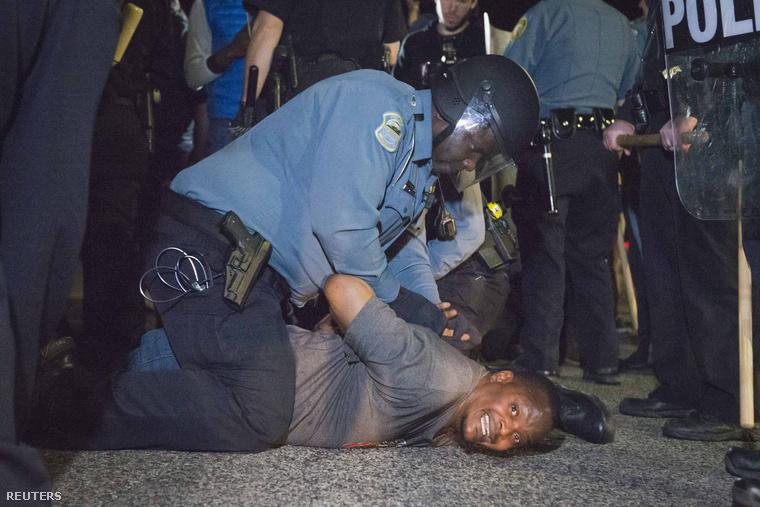 Rendőrök tepernek le egy férfit a lövöldözést követő dulakodás után a tüntetés helyszínén.