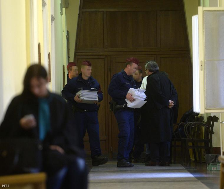 Rendőrök viszik a Buda-Cash-ügy iratait a Fővárosi Törvényszék Fő utcai épületében 2015. március 11-én, ahol az ügy kapcsán március 9-én őrizetbe vettek előzetes letartóztatásáról döntött a bíróság.