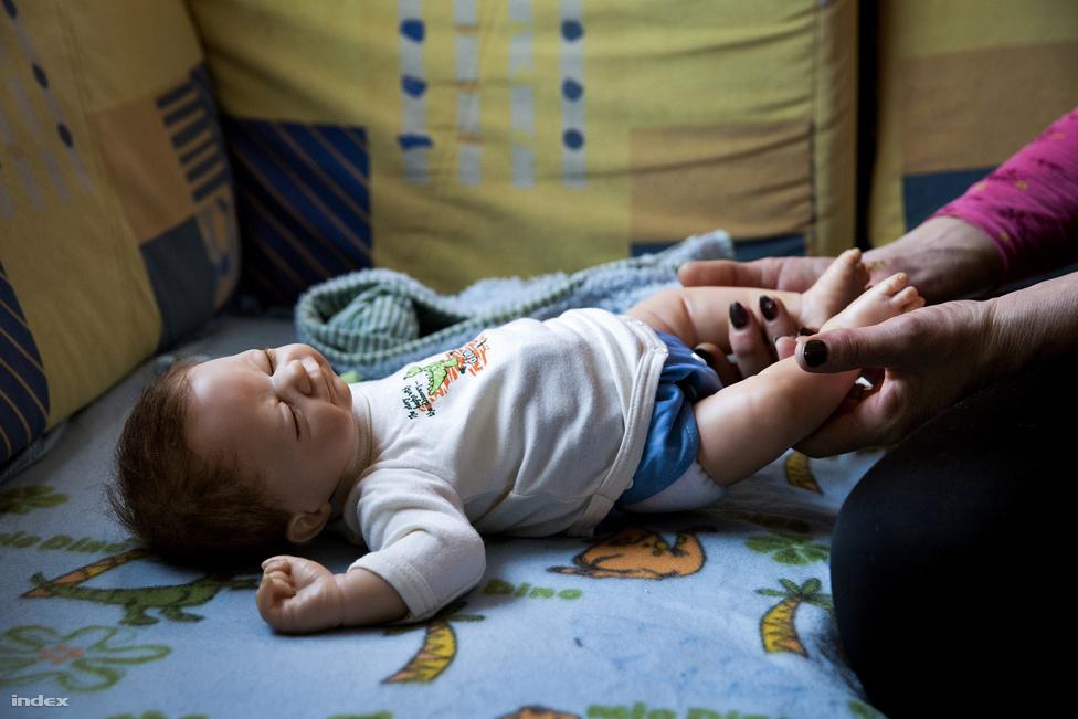 """""""Én nem megrendelésre vettem a babát, hanem egy kész babába szerettem bele, egy készítő, Horváth Mónika weboldalán lévő fotó alapján láttam meg Tinát. Aznap, amikor mentem érte, annyira izgultam, mint egy szűzlány az első aktus előtt. Érkezéskor egyből láttam, hogy a sok baba között melyik az enyém. 2,6 kg volt és 56 centi, igazi újszülött. Eleinte megállás nélkül csak öltöztettem, fésülgettem fésüléskönnyítő szerekkel, tisztogattam, szeretgettem"""" - meséli, miközben átöltözteti Csegőt. """"Aztán nagyon beteg lettem, és el kellett adnom Tinát, ami azóta is nagy fájdalom."""""""