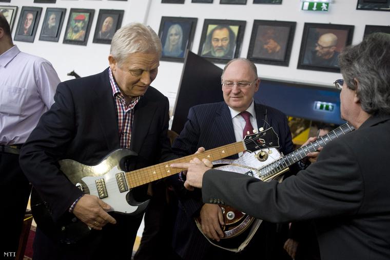 Tarlós István főpolgármester (b) és Tóth József, a XIII. kerület polgármestere (k) gitárokat próbálnak ki a Rockmúzeum megnyitóján az angyalföldi RaM Colosseumban 2014. február 6-án