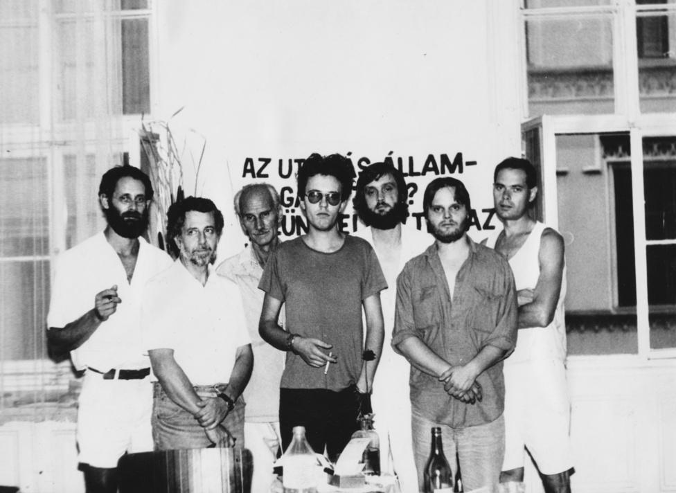 1988. A rendszerváltás küszöbén sorra alakultak a különféle szervezetek, köztük az Országos Dohányfüstmentes Egyesület is. Ha a képet jobban megnézzük, akkor rögtön észrevesszük, hogy a képen látható férfiak minden bizonnyal nem e szervezet nevében léptek fel, és néztek a kamerába. A nyolcvanas évek végén a magyar férfilakosság több mint ötven százaléka dohányzott, itt csak ketten, Philip Tibor és Pálinkás Róbert kezében láthatunk cigarettát. A Beszélő köréhez tartozó hét férfi éhségsztrájkol éppen, azt szeretnék, ha alanyi jogon, nem politikai megfontolások alapján járna útlevél. Az esemény arról nevezetes, hogy a korabeli mainstream sajtóban ekkor jelenhettek meg először ellenzékiek nem rendőrségi hírként. A képen látható nemdohányzók is megérdemlik, hogy kiírjuk a nevüket: Kőszeg Ferenc, Pákh Tibor, Kelemen Ferenc, Bokros Péter, dr. Erdei Gyula.